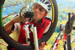 Man cyclist repairing a bike  against blue sky - stock photo