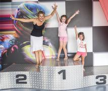 A mother and her daughters on a podium of competition - stock photo