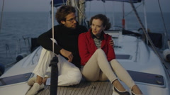 Young couple relaxing on a yacht in the sea in the evening at sunset Stock Footage