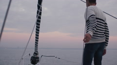 Man raises hands in a relaxing way on a sailboat in the sea - stock footage