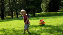 Child carefully pulls a toy truck with toys Stock Footage
