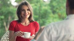 Young couple talking and drinking coffee in outdoor cafe in park HD - stock footage