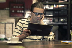 Young woman watching movie on tablet, by table at home at night NTSC Stock Footage