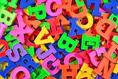 Colorful plastic alphabet letters as background - stock photo