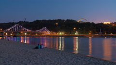 People sit on the beach picturesque embankment by night city and bridge lights - stock footage