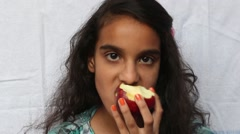 A girl child eating apple Stock Footage