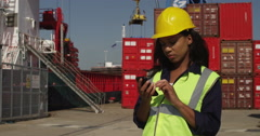 An attractive female worker talking on a mobile phone at a busy shipyard. Stock Footage