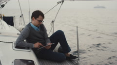 Man uses tablet on a yacht in the sea - stock footage