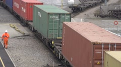 Dockyard shipping containers pulled on train with workmen walking beside Stock Footage