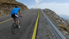 Lone cyclist climbing a slope paved road 96 Stock Footage