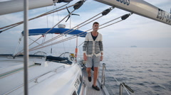 Young man in shorts walks on yacht in the sea Stock Footage
