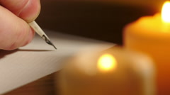 Writing with quill pen by candlelight Stock Footage