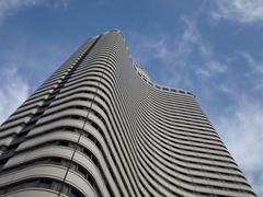 Skyscraper building in wavy design over blue sky Kuvituskuvat