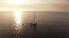 Aerial drone shot of a sailing boat in the sea at sunset - stock footage