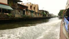 POV from express boat sailing along city canal, low-rise poor hovels on bank Stock Footage
