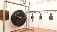 Large hanging gong with stick, suspended bells against white wall, monastery Stock Footage