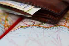 Euro banknotes inside wallet on a geographical map of Monaco - stock photo