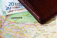 Euro banknotes inside wallet on a geographical map of Dresden - stock photo