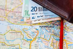 Euro banknotes inside wallet on a geographical map of Hamburg - stock photo