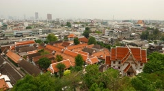 Wat Saket roofs, aerial view, wide angle shot from above, pan left Stock Footage