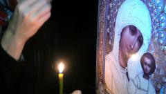 The girl with the candle prays before of the Orthodox icon Stock Footage