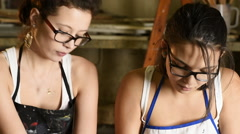 Two young female art students kneading clay for sculpting Stock Footage