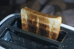 White dirty toaster and burned toast (selective focus, dark tone) Stock Photos