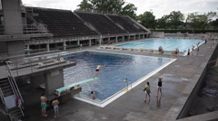 Man jumps off diving board at Berlin Olympic Stadium pool, Germany Stock Footage