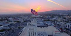 Aerial view American US flag rooftop city Los Angeles cityscape at sunset 4K UHD Stock Footage