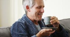 Mid-age white man enjoying morning cup of tea - stock photo