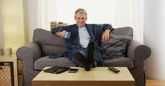 Cheerful middle-aged man relaxed on couch with feet on table Stock Photos