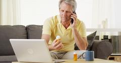 Middle-aged man reading medication prescription and talking on the phone Stock Photos