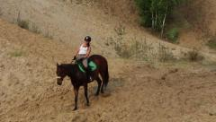 Girl riding a horse on sandy hills - stock footage