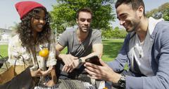 Stock Photo of Mixed ethnic friends hanging out at the park