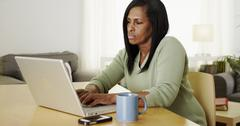 Serious mature black woman searching the internet - stock photo