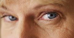 Beautiful mature woman blue eyes closeup Stock Photos