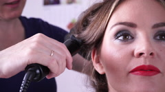Hairdresser curling woman hair with electric iron curler 4K Stock Footage