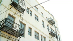 Establishing shot of an apartment building with fire escapes Stock Footage