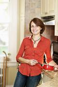 Smiling woman in kitchen at home Stock Photos