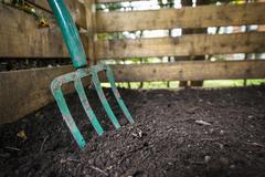 Garden fork turning compost - stock photo