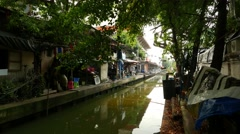 Slum aside tiny canal, old Bangkok, elderly man walk along concrete walkway Stock Footage