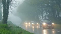 Cars Pass Through Woods In Rain And Fog Stock Footage