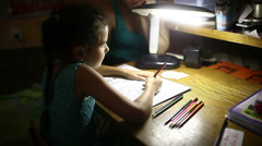 Teen in the evening doing homework lessons girl draws light from the lamp Stock Footage