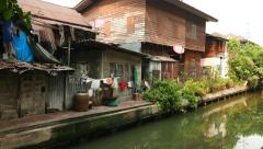 Vendor cart parked aside canal, poor hovels nested against, opposite bank Stock Footage