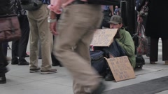 People walking past a homeless man Stock Footage