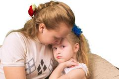 Elder sister consoles the younger isolated on white Stock Photos
