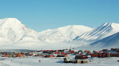 Small town among snow-capped mountains of the Norwegian archipelago of Svalbard. - stock footage