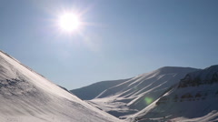 Snow-covered peaks of the Northern mountains and the sun. Stock Footage
