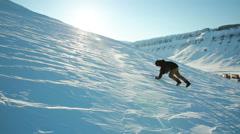 A man trying to climb the mountain on a slippery frozen snow, slips and falls. - stock footage