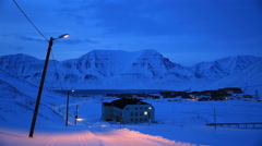 A small town in the far north of Europe among the snow-capped mountains at night - stock footage